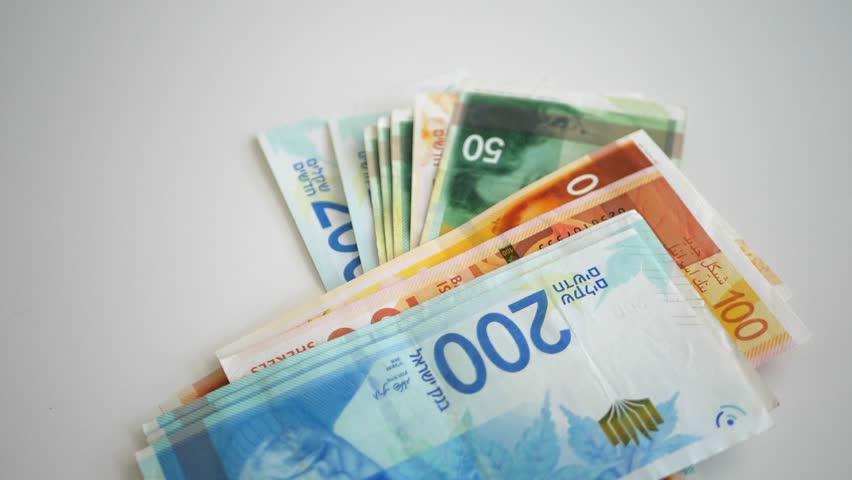 Israeli New Shekel Money Bills Fall on Table