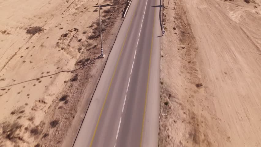 road in the desert, a car follow is way