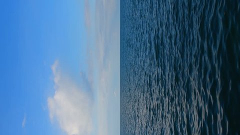 Sea seamless loop background. Sea view at sunny day, blue sky with clouds, ripple on the surface of sea, clear horizon line. Vertical nature background full HD resolution 1080x1920 for mobile screen.