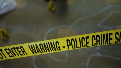 Camera pans across yellow police tape at an active crime scene