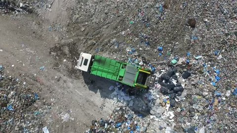 Garbage truck spills rubbish in a dump, aerial view