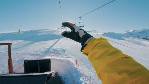 Man sits on ski lift going up mountain, shows shaka sign or hipster hang loose gesture on camera, plays with sun leak and beams, actuve lifestyle choice and leisure hobby winter activity