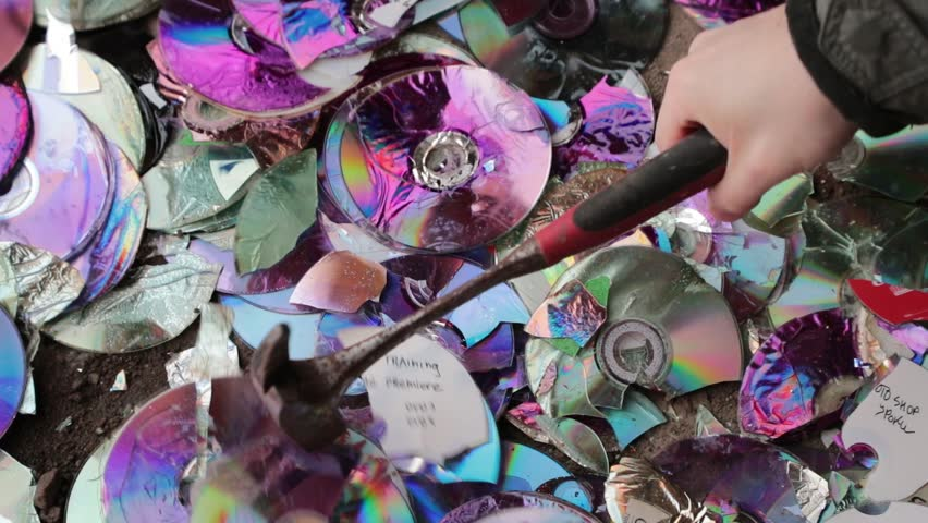 break compact discs with a hammer. slow motion video