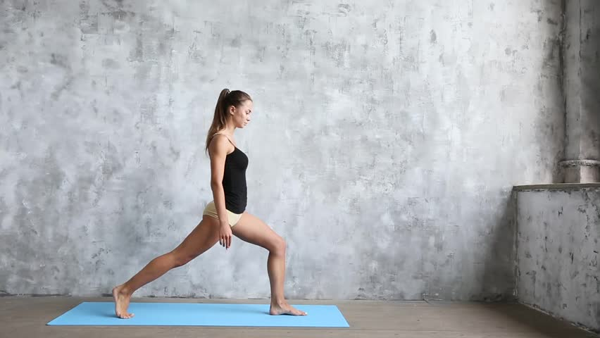 Woman practicing yoga indoors on blue mat. Wellness concept. #1007168665