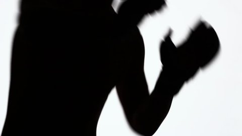 Silhouette of a sporting young man during training on fights without rules. Strikes with fists and elbows. Close-up of a profile of a hand and a torso with muscles. Black object isolated on white.
