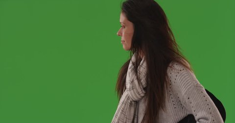 Profile portrait of young woman with somber expression looking away on green screen. Closeup of beautiful young woman looking desolate on greenscreen. 4k
