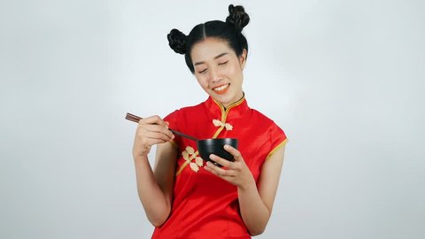 4k video of happy woman wearing chinese cheongsam dress playing chopsticks and bowl on a white background