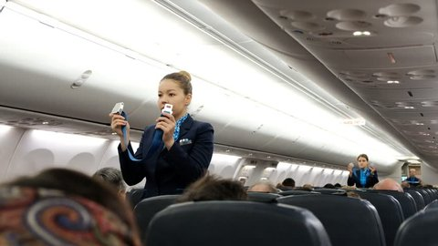 Cologne, Germany, 16 of december 2017: Flight attendant Show how to deal with seat belt on board of one of Pobeda-airlines low coster company aircrafts.