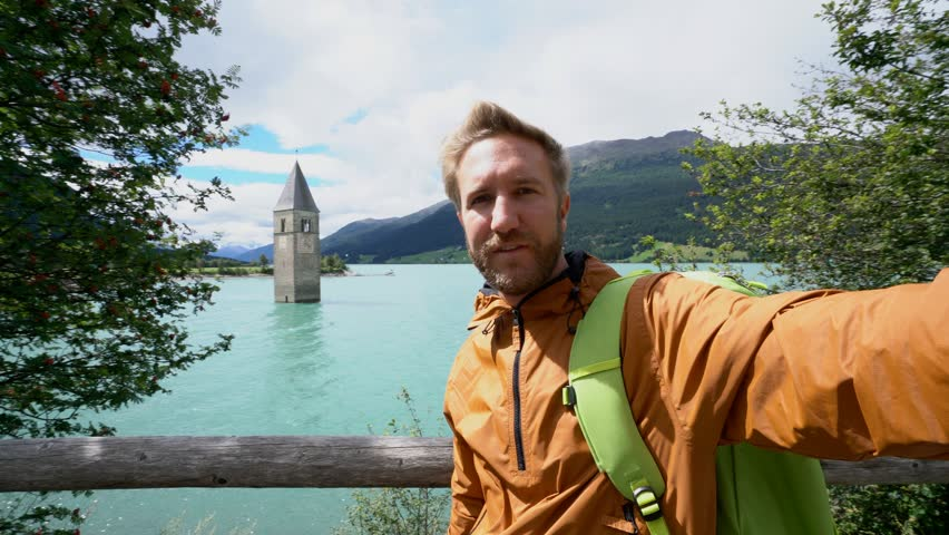 Travel male taking selfie at Lago di Resia, northern Italy. Man takes a selfie in Resia lake, stunning mountain scenery, clock tower church in the background. Man taking selfies pov