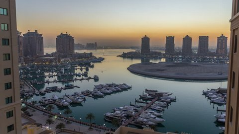 Evening at the Pearl-Qatar day to night timelapse from top. It is an artificial island in Qatar. View of the Marina and residential buildings in Porto Arabia in Doha, Qatar, Middle East