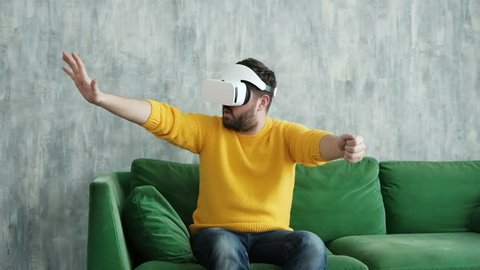 Future is now. Handsome man playing game in vr glasses. Man touch something using modern virtual reality glasses