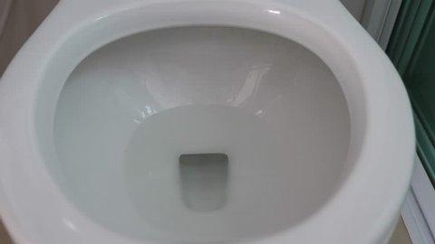 Close up flushing toilet