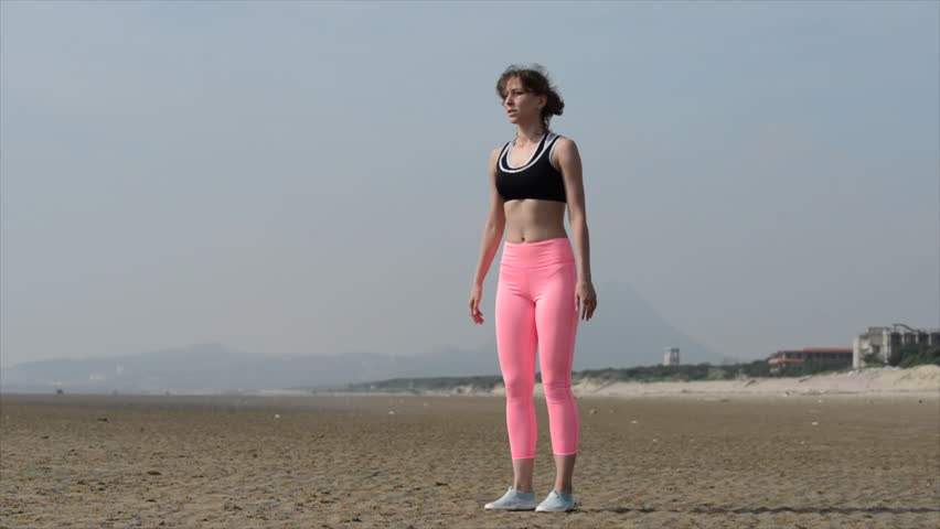 Beautiful young woman with sport sexy body doing workout warm up in ocean beach Hong Kong. Outdoor sport shooting with attractive female model | Shutterstock HD Video #1007380135