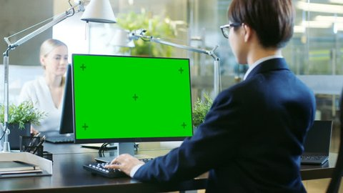 In the Office East Asian Businessman works on a Desktop Personal Computer with Mock-up Green Screen. He Dramatically Turns Head, Looks over the Shoulder into the Camera. Colleague Enters Office and Ta