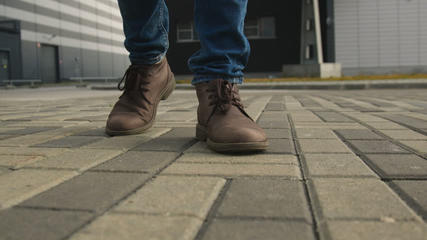 The one guy confidence walks along the town footway in jeans and stylish brown leather shoe. Point of view from first person on legs closeup. Spring cold weather, pedestrian go up front slow motion | Shutterstock HD Video #1007405065