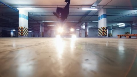 Young stylish man freerunner performing a handstand, parkour acrobatic elements, slow motion