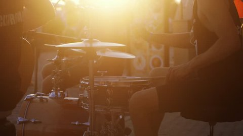 Close up of music group are playing drums on promenade at amazing golden sunset and lens flare effect. slow motion. 3840x2160