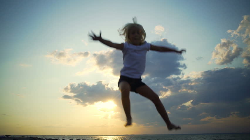 Blonde baby girl at trampoline background sky sunset rapid slow motion