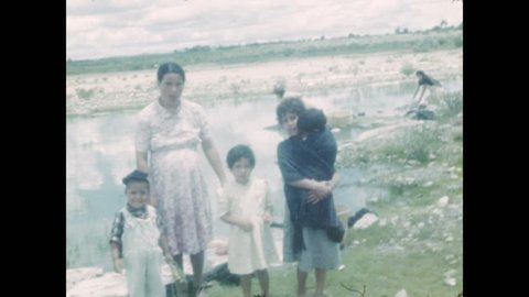 1940s: Mexican family stands by a pond. Women kneel next to pond doing laundry. State limit sign leaving Jalisco and entering Zacatecas. Open road driving on rural roads with stone sides.