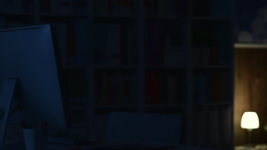 Man sitting at desk late at night and connecting with his computer, he is social networking and typing | Shutterstock HD Video #1007489137