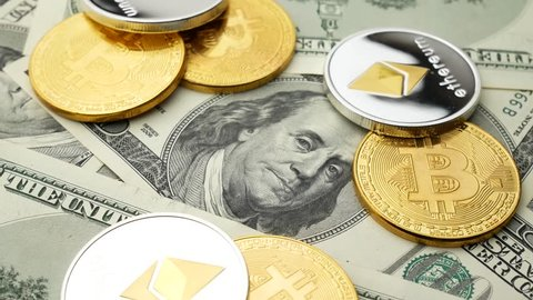 Bitcoin BTC coin and Ethereum ETH coins rotating on bills of 100 dollars