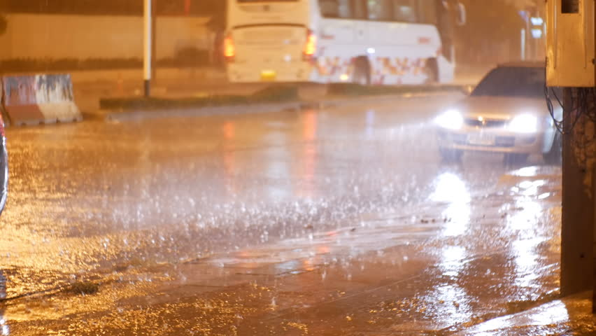 Tropical rainfall at night on the road in Asia. Cars stand and ride under heavy rain. Drops of rain sprinkle on the asphalt. Thailand. Pattaya