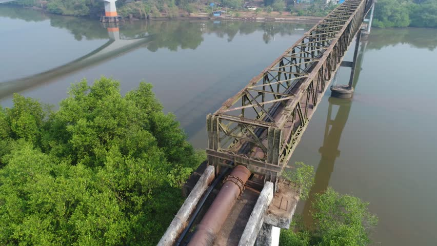 Rusty metal truss aqueduct over the water. Water supply through the pipe from one Bank of the river to another. Flying around aqueduct quickly. Shooting with a drone. | Shutterstock HD Video #1007525998