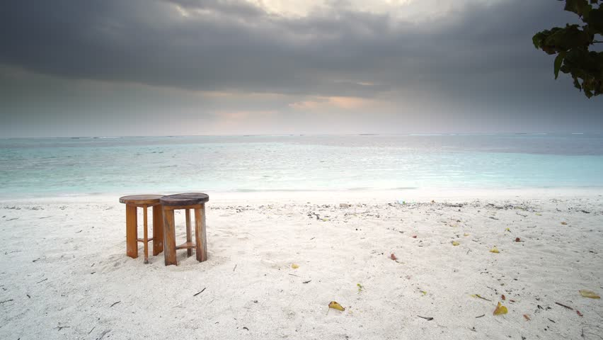 Beautiful scenery at sandy beach of Maldives with two wooden chairs in frame