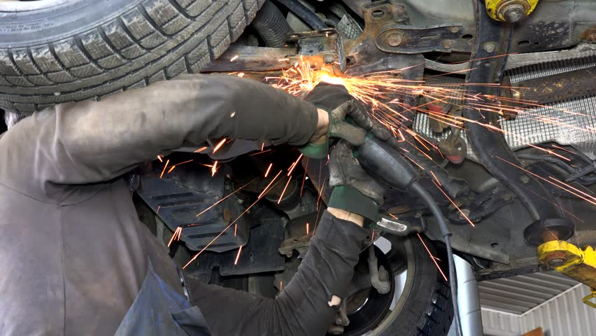 sparks coming from steel grinder. male worker cutting rusty car parts in his work place.