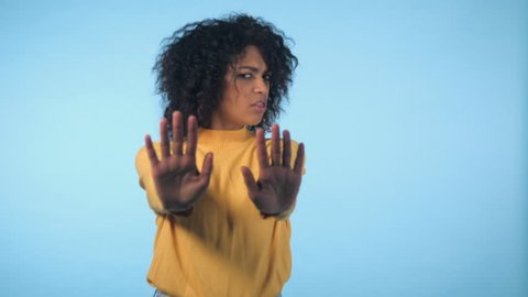 Angry annoyed woman raising hand up to say no stop. Sceptical and distrustful look, feeling mad at someone. Afro girl facial expressions, emotions and feelings. Body language