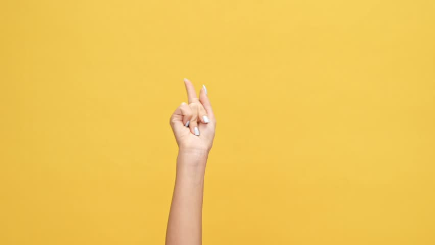 Woman hand pointing at someone over yellow background