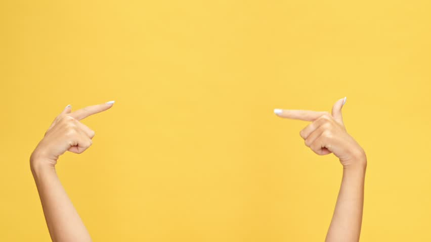 Woman hands pointing on copyspace and showing thumbs up over yellow background  | Shutterstock HD Video #1007574865