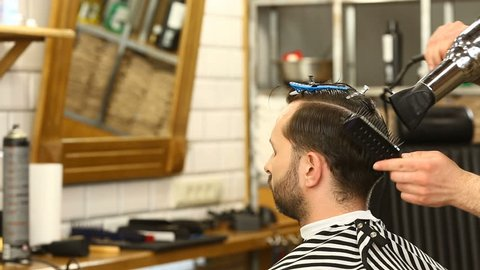 Barber blowdries and combs client's hair using hairdrier and brush in Barbershop. Profile of young man having his hairstyle done at barber's, hd