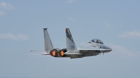 Full Afterburner Military Combat Jet Aircraft just after Takeoff in Slow Motion 96fps Low Pass over the Runway. United States Air Force McDonnell Douglas F-15C Eagle at Plovdiv Air Base 24 June 2016