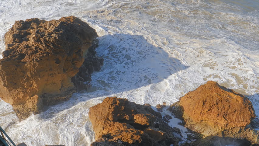 Rocks and waves of surf in the ocean, stairs of Farol De Nazare coast, Nazare, Portugal