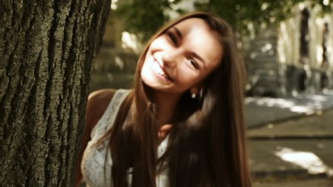 coquettish young woman peeks out hiding tree flirty smiles
