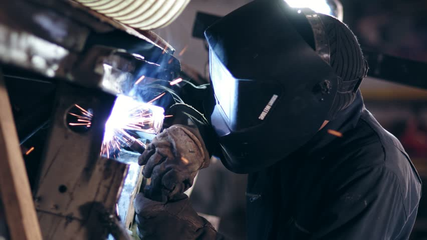 Male worker at a welding factory in a welding mask. Welding on an industrial plant. Slow motion.