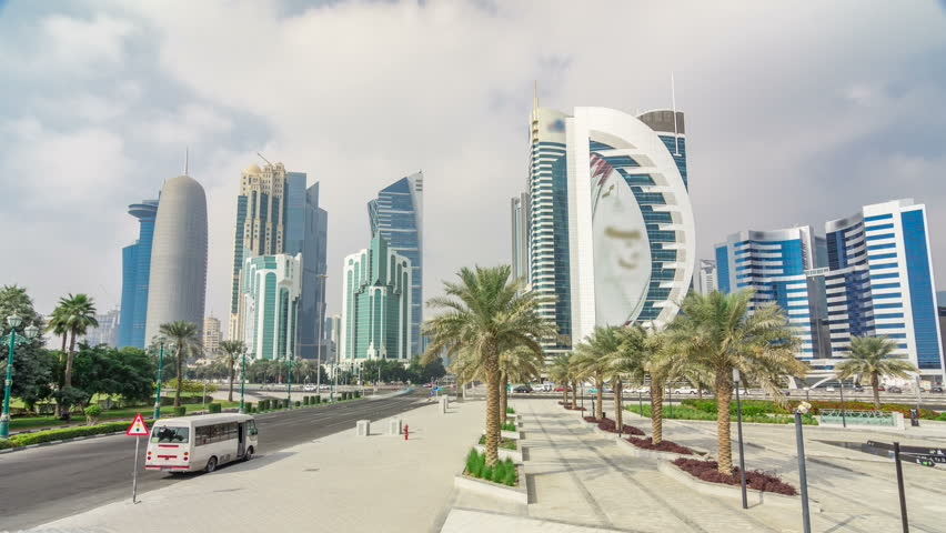 The high-rise district of Doha timelapse hyperlapse with traffic on intersection, seen from the Hotel Park, with skyscrapers and palms