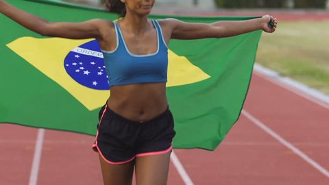 Mixed-race female athlete running on stadium with flag of Brazil, patriotism