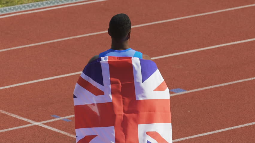 Excited champion showing flag of Great Britain to supporters, pride of nation | Shutterstock HD Video #1007644303