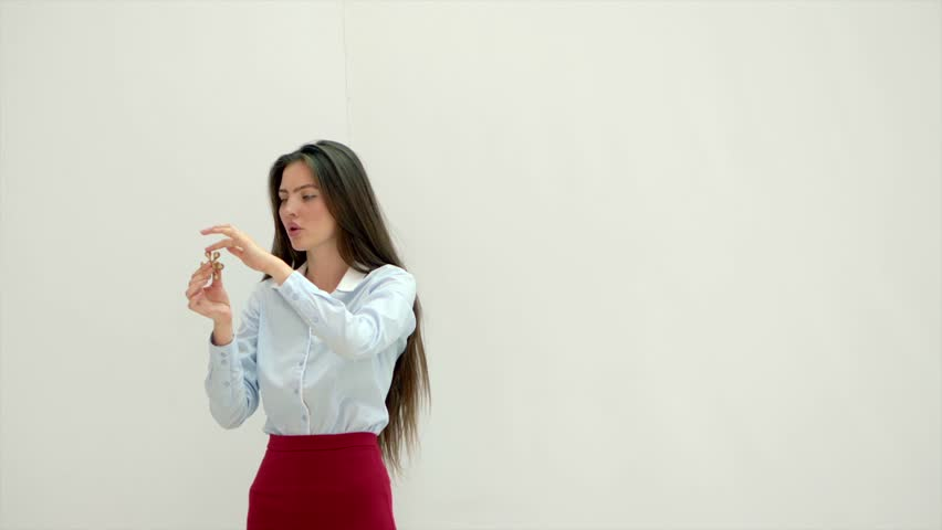 Wonderful young girl is standing against white wall and playing with a spinner. She is watching it rolling in her hand. | Shutterstock HD Video #1007646811