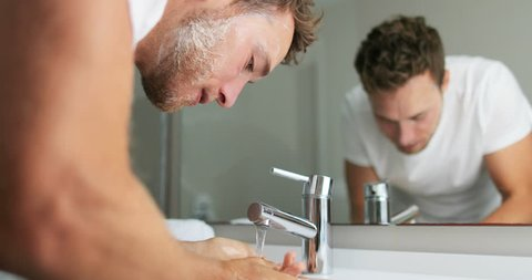 Man washing face rinsing soap from skin in sink under running cold water from faucet,