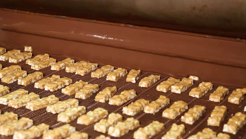 Bars of nougat with nuts are poured with chocolate. Manufacture of chocolate bars with nougat and peanuts. Chocolate bars move along conveyor belt at confectionery factory for the production of sweets