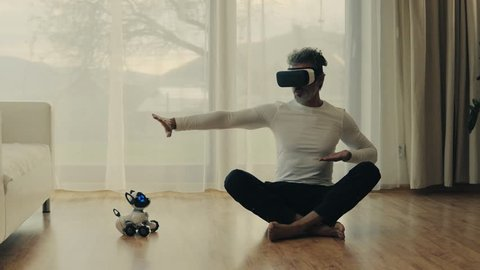Mature man with VR goggles and robot smart dog at home.