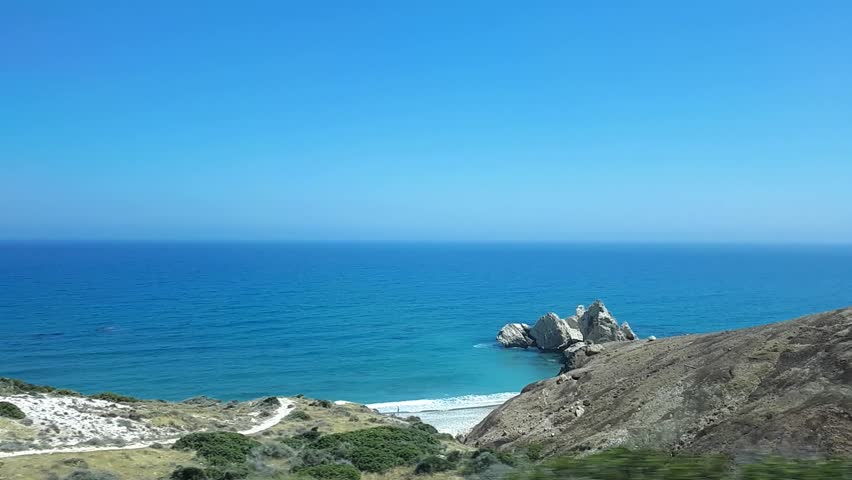 Beautiful view from the window of a moving train, bus or car. Panoramic view through the window of moving transport, scenic sea landscape outside the window on a sunny summer day. Cyprus