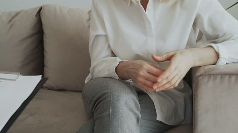 Close-up of woman nervously gesturing and moving hands while talking to male psychoanalyst in office