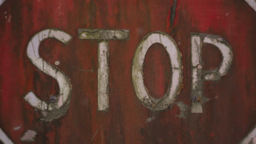 Stop sign. Old shabby and rusty road sign. Entry into the forbidden zone. Abandoned road. The order will stop. A shabby stop sign before entering the abandoned city. 4K (UHD). 2 shots