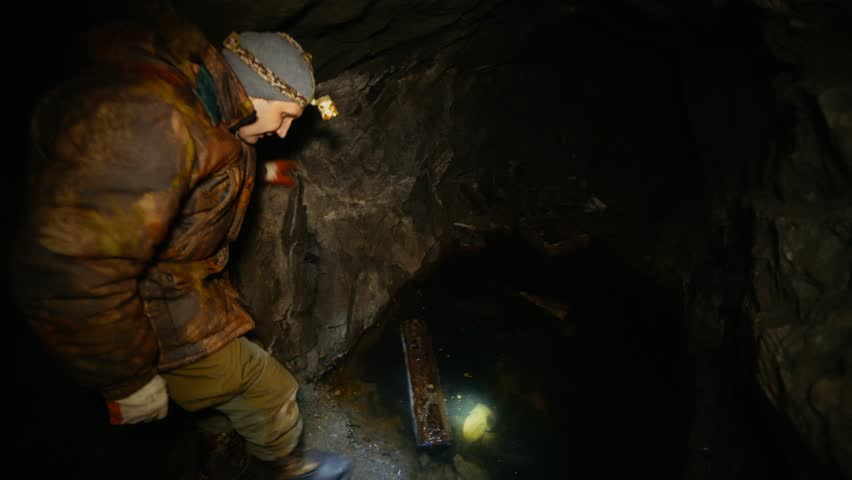 A man in the dark with a flashlight in an abandoned mine finds wooden supports | Shutterstock HD Video #1007682715
