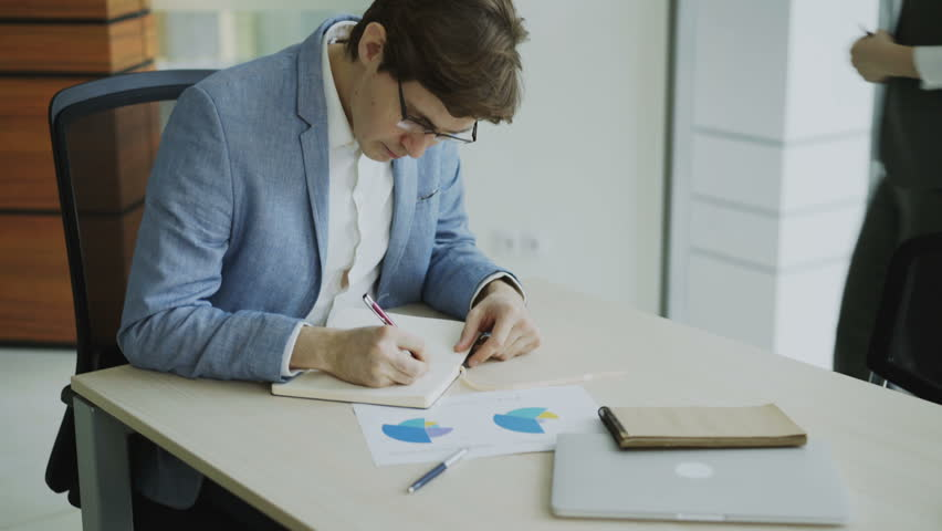 Two business colleagues discussing reports in modern office. Businessman sitting at the table talking his female partner | Shutterstock HD Video #1007692120