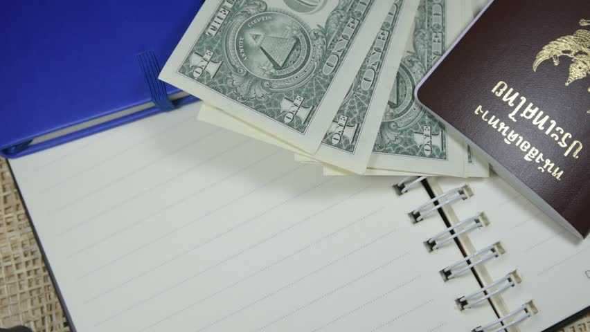 People are counting the dollar of America and the Thai passport is placed on the table,The use of dollars for cheap travel abroad,The use of dollars for foreign purchases.    Shutterstock HD Video #1007708125